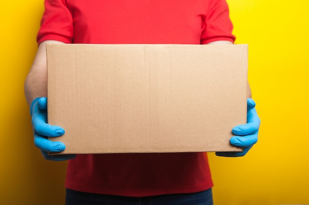 Online ordering and delivery. a man in a red uniform and rubber medical gloves holds a box on a bright yellow . food delivery during the coronavirus quarantine period.