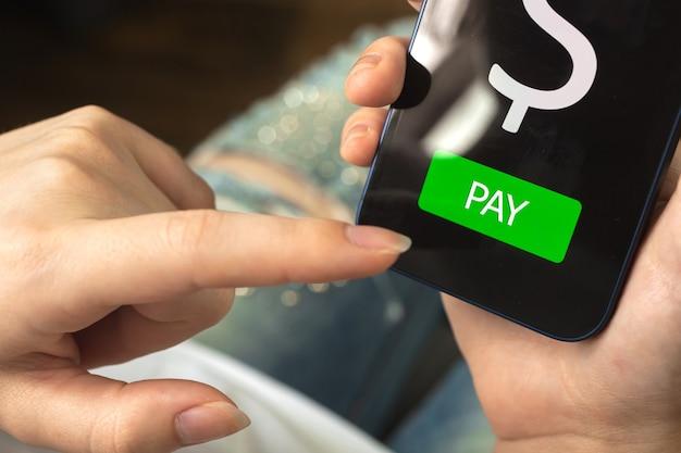 온라인 지불 개념, 화면의 지불 버튼, 스마트폰을 고소하고 온라인 뱅킹 애플리케이션을 사용하는 여성, 전자 상거래 개념 사진