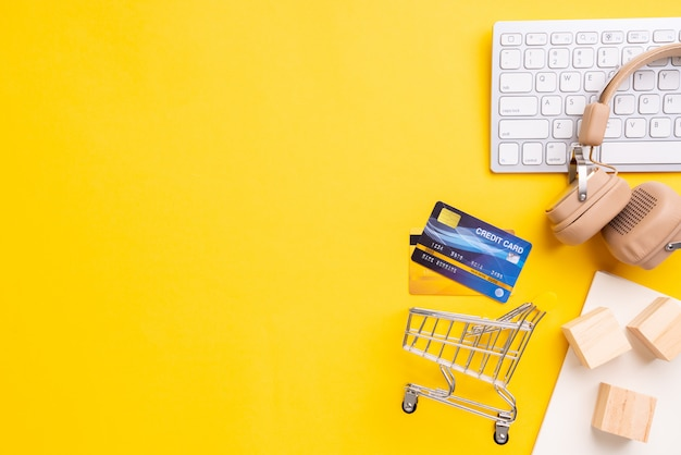 Online payment  concept with shopping cart top view and yellow background