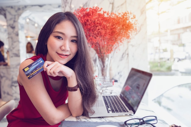 Online payment concepts, young asian woman smiling holding credit card in hands while shopping online on laptop in coffee shop