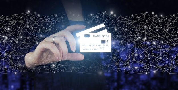Online payment, financial futuristic and technology, credit card are design up. hand hold digital hologram credit card sign on city dark blurred background. online payment digital and shopping.