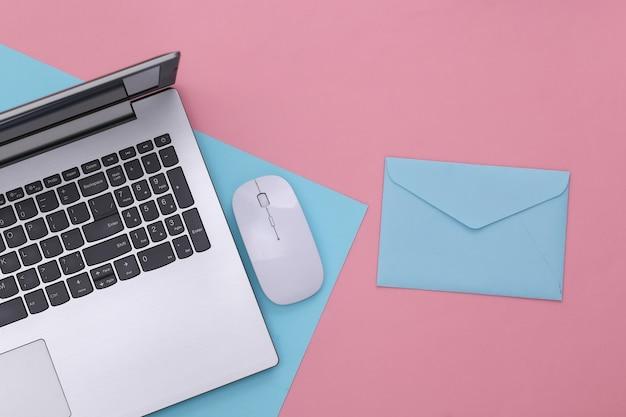 オンライン支払い。 pcマウス、ピンクブルーパステル背景の封筒とラップトップ。上面図。