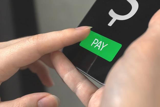 온라인 결제 모바일 기술. 스마트폰을 사용하는 여성의 손과 화면의 지불 버튼을 터치하는 모바일 뱅킹 개념 사진