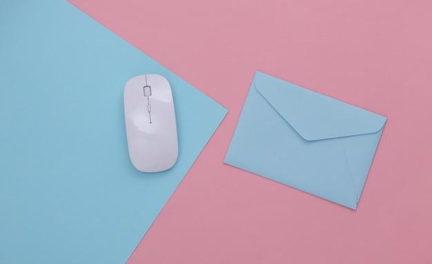 オンライン支払い。 pcマウス、ピンクブルーのパステルカラーの背景に封筒。上面図。