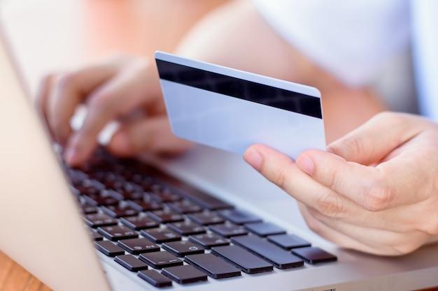 オンライン支払い 。クレジットカードを保持し、ラップトップを使用して女性の手。オンラインショッピング