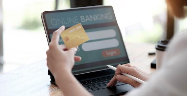 オンライン支払い、クレジットカードを保持し、ビンテージフィルタートーンでオンラインショッピングにラップトップコンピューターを使用する女性の手