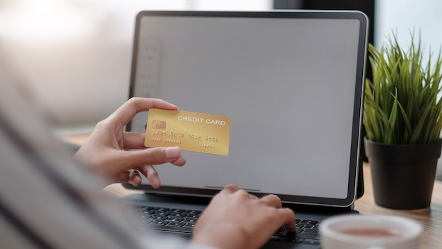 Online payment,woman's hands holding a credit card and using laptop computer for online shopping with vintage filter tone