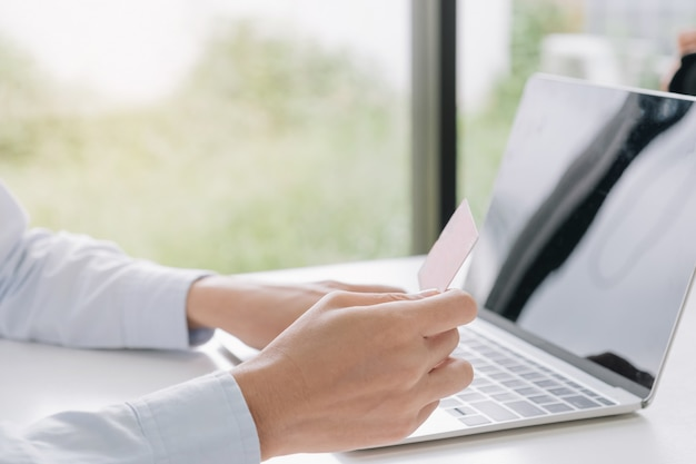 Online payment, woman's hands holding credit card and using notebook for online shopping