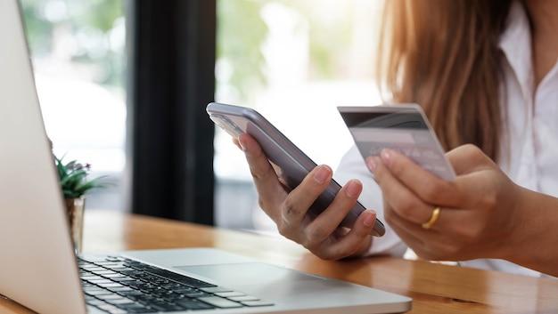 スマートフォンを持ち、オンラインショッピングにクレジットカードを使用するオンライン決済の女性の手。サイバーマンデーのコンセプト