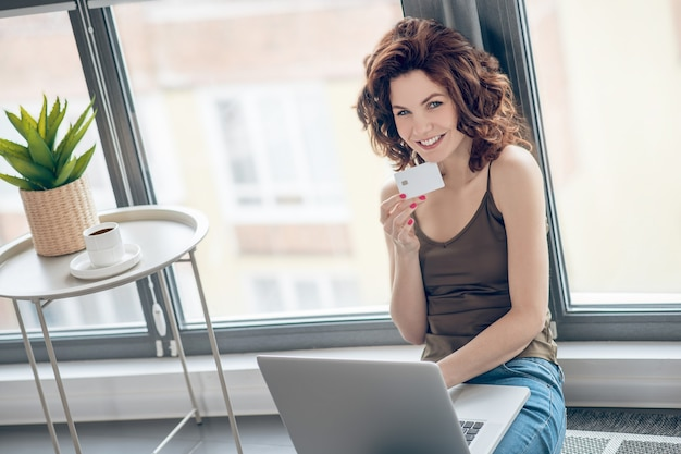オンライン決済。クレジットカードを保持し、オンライン決済を計画している黒髪のきれいな女性