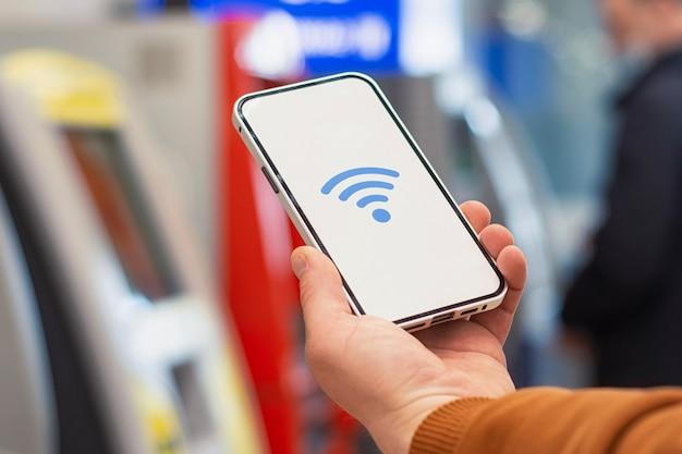 온라인 결제. Atm 현금 인출기를 배경으로 Wi-fi 아이콘이 있는 전화 디스플레이. 남자는 그의 손 클로즈업에 스마트폰을 보유하고 있습니다. 프리미엄 사진