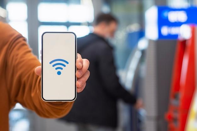 온라인 결제. atm 현금 인출기를 배경으로 wi-fi 아이콘이 있는 전화 디스플레이. 남자는 그의 손 클로즈업에 스마트폰을 보유하고 있습니다.