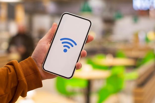 Онлайн-платежи. дисплей телефона со значком wi-fi на фоне ресторана. мужчина держит смартфон в руке крупным планом