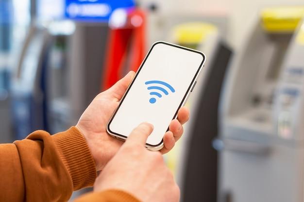 온라인 결제. atm 현금 지급기를 배경으로 wi-fi 아이콘이있는 전화기 디스플레이
