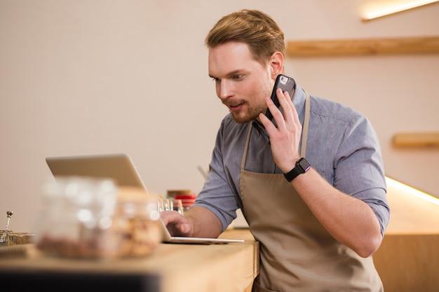 온라인. 노트북을 사용하고 카페에서 일하는 동안 전화로 이야기하는 즐거운 젊은 남자