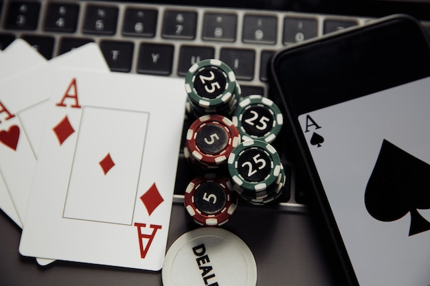 Тема онлайн-казино в покере. крупный план игровых фишек, смартфона и игральных карт на клавиатуре