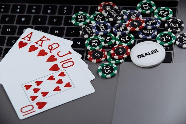 オンラインポーカーカジノのテーマ。ラップトップ上のギャンブルチップとトランプ。