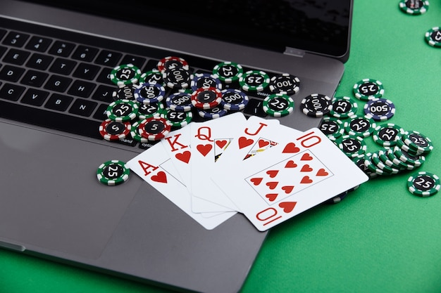 Online poker casino theme. gambling chips, playing cards anf laptop on green background.