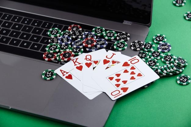 オンラインポーカーカジノのテーマ。ギャンブルチップ、トランプ、緑の背景のラップトップ。