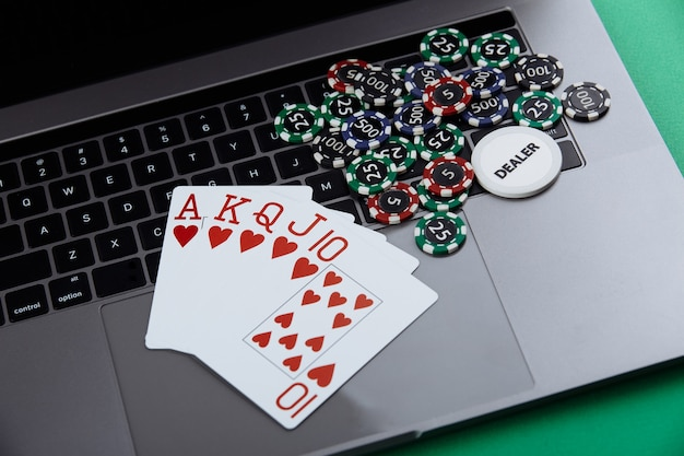 Online poker casino theme. gambling chips and playing cards on laptop.