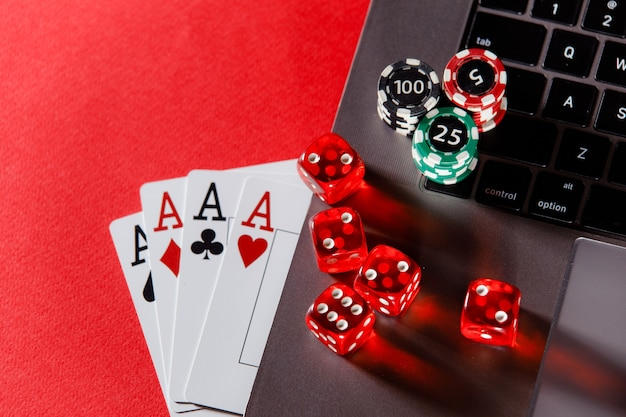 Online poker casino theme. gambling chips and playing cards on a red background.