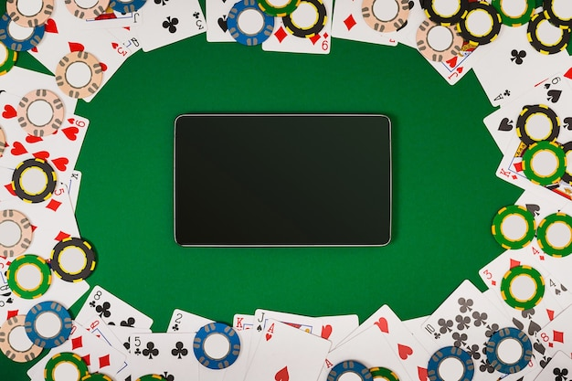 Online poker game with digital tablet, chips and cards. view from above with copy space. banner template layout mockup for online casino. green table, top view on workplace.