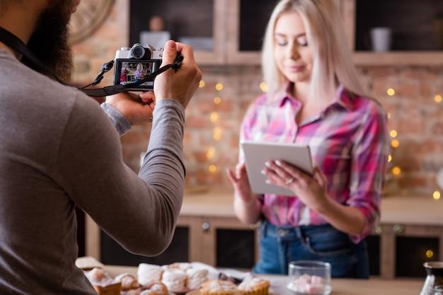 온라인 레시피. 블로깅. 태블릿을 가진 여자입니다. 케이크와 패스트리 요리에 대한 동영상 블로그 에피소드를 촬영하는 사람.