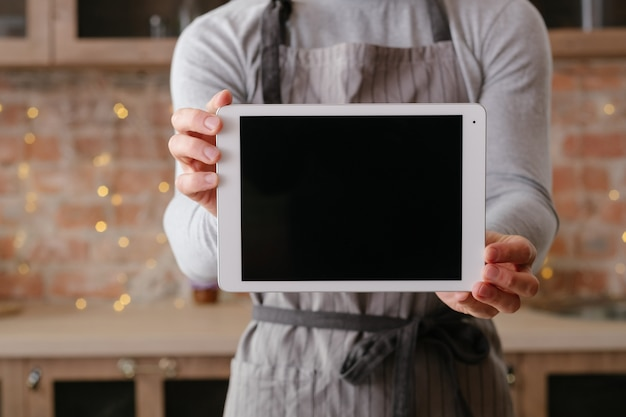 온라인 레시피. 남자 손에 검은 화면 태블릿. 광고. 로프트 주방 공간. 앞치마에서 요리