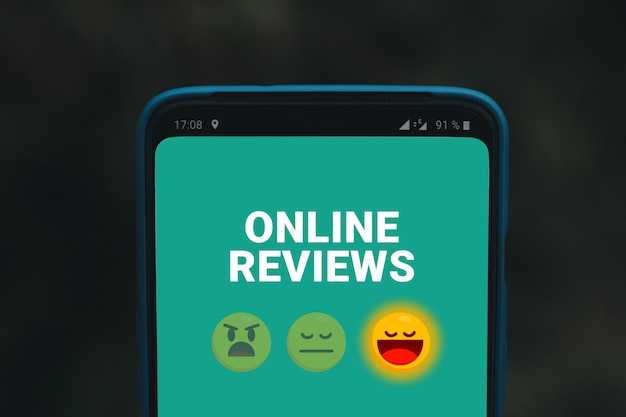 Online reviews services or organization. mobile phone screen with emoticons smiles