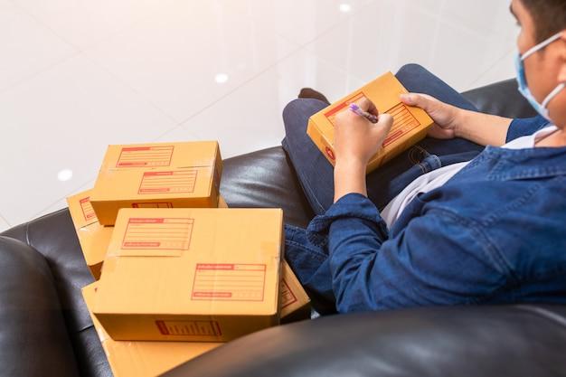 Онлайн-продажи молодые начинают малый бизнес в картонной коробке на работе.