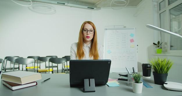 オンライン教育、eラーニング。女教師は、tabletpcを使用してリモートでオンラインレッスンを行っています。