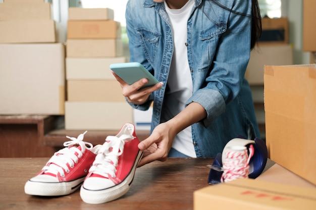 Владелец интернет-продавца делает фото товара для загрузки в интернет-магазин на сайте. интернет-продажи, интернет-магазины и концепция электронной коммерции.