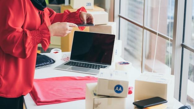 オンライン販売者はホームオフィスで働いており、顧客への配送ボックスを梱包します。