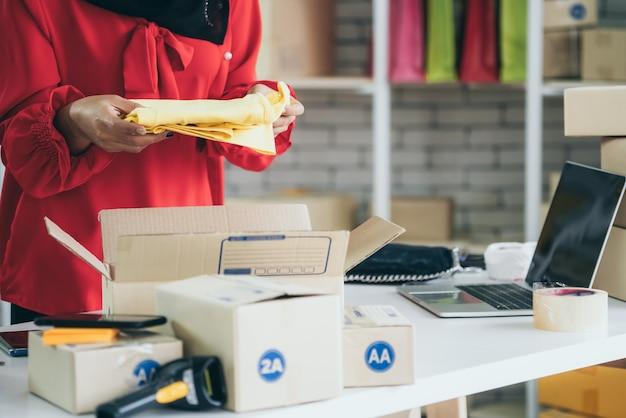 온라인 판매자는 본사에서 근무하며 배송 상자를 고객에게 포장합니다.