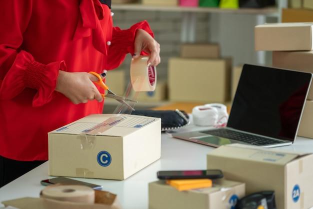 Онлайн продавец работает в домашнем офисе и упаковывает доставленную коробку доставки клиенту.