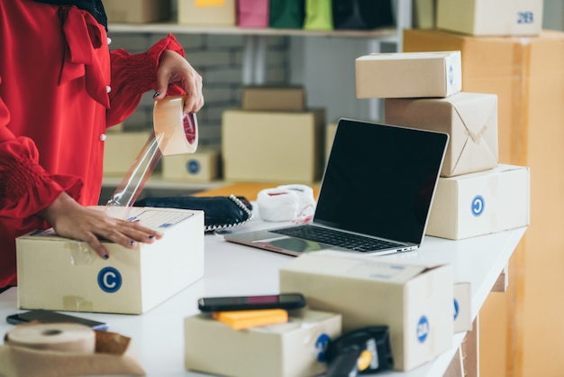 オンライン販売者はホームオフィスで作業し、顧客への配送用宅配ボックスを梱包します。