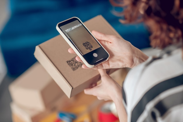 Online shop worker scanning information on the product package