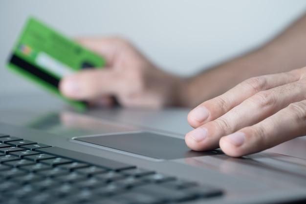 온라인 쇼핑객은 노트북을 사용합니다. 그는 신용 카드로 지불합니다.