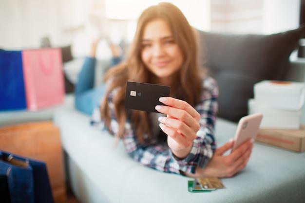オンラインショッピング。若い女性が自宅のソファーに横になり、クレジットカードの板のクローズアップをカメラに見せています。