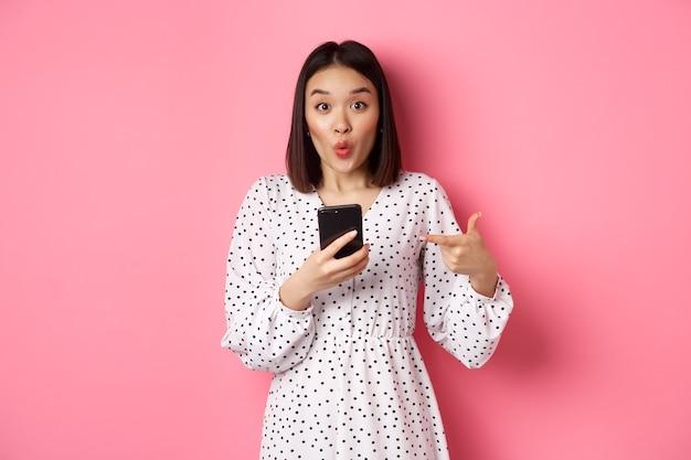 온라인 쇼핑 및 미용 개념. 휴대 전화에서 손가락을 가리키는 놀된 아시아 여자, 스마트 폰 앱 추천, 분홍색 위에 서.