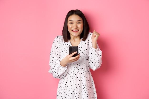온라인 쇼핑 및 미용 개념. 인터넷에서 승리하고, 스마트 폰을 들고 기뻐하고, 행복하고 축하하고, 분홍색 위에 서있는 흥분된 아시아 여성.