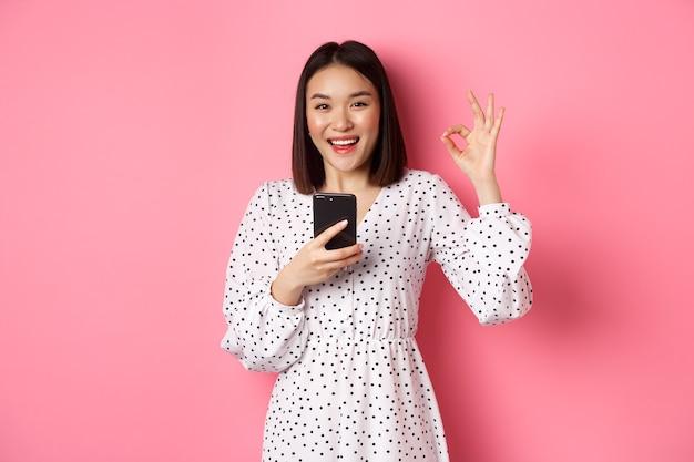 Интернет-магазины и концепция красоты. удовлетворенная азиатская клиентка показывает нормально, делает покупку в интернете на смартфоне, стоя на розовом фоне.