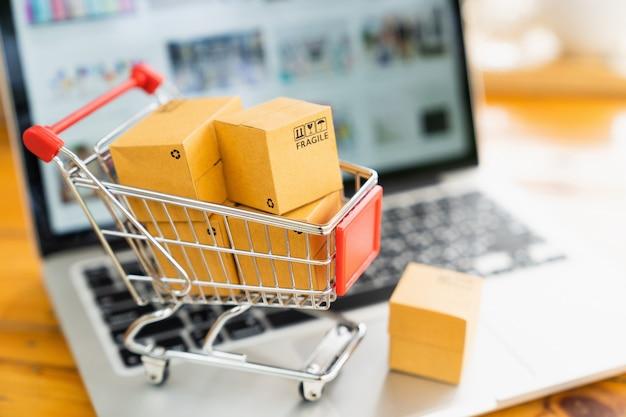 Онлайн концепция покупок и доставки, коробки пакета продукта в тележке и портативный компьютер.