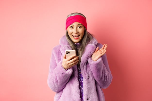온라인 쇼핑 및 패션 개념. 분홍색 스마트 폰에서 인터넷 프로모션 제안을 확인하면서 흥분된 아시아 성숙한 여인