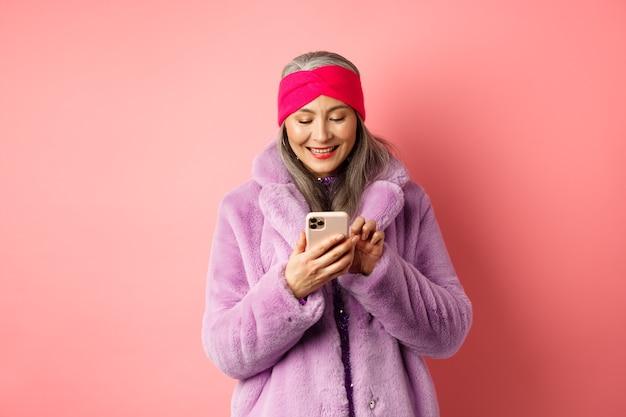 온라인 쇼핑 및 패션 개념. 트렌디 한 가짜 모피 코트 문자 메시지에 현대 아시아 할머니, 스마트 폰을 사용하고 분홍색 화면에서 행복하게 보입니다.