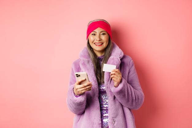 オンラインショッピングとファッションのコンセプト。ピンクの背景に幸せに立って、携帯電話とプラスチックのクレジットカードを使用してスタイリッシュな毛皮のコートで中年女性の笑顔