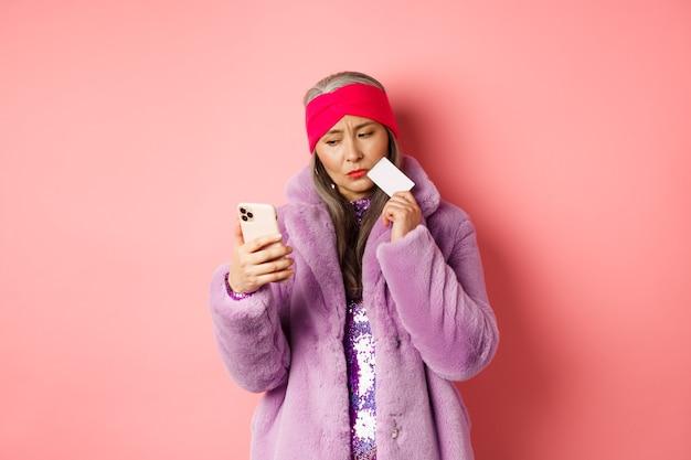 온라인 쇼핑 및 패션 개념. 분홍색에 플라스틱 신용 카드를 들고 스마트 폰 화면에서 우유부단하게 보이는 보라색 인조 모피 코트에 세련된 아시아 아가씨.