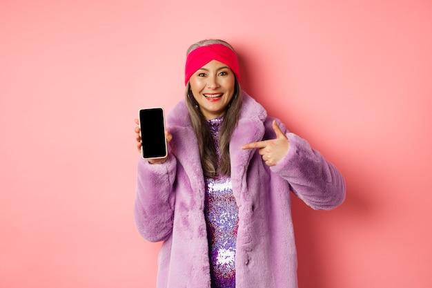 온라인 쇼핑 및 패션 개념. 세련 된 아시아 성숙한 아가씨 빈 스마트 폰 화면을 보여주는, 전화를 가리키고 분홍색에 웃 고.