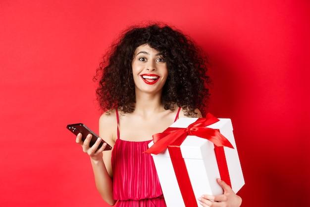 オンラインショッピングとバレンタインデー。スマートフォンと恋人の贈り物を持って、カメラ、赤い背景に驚いて幸せそうに見える美しい若い女性。