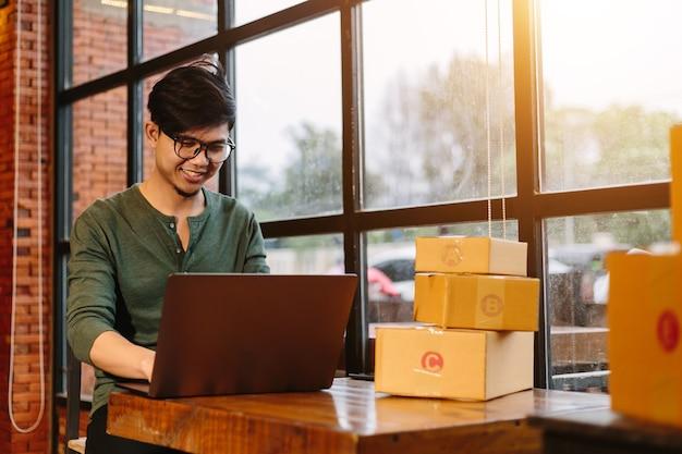 オンラインショッピングのアジアの若者は、仕事で段ボール箱で中小企業を始めます。売り手は、顧客、オンライン販売、またはeコマース用の宅配ボックスを準備します。